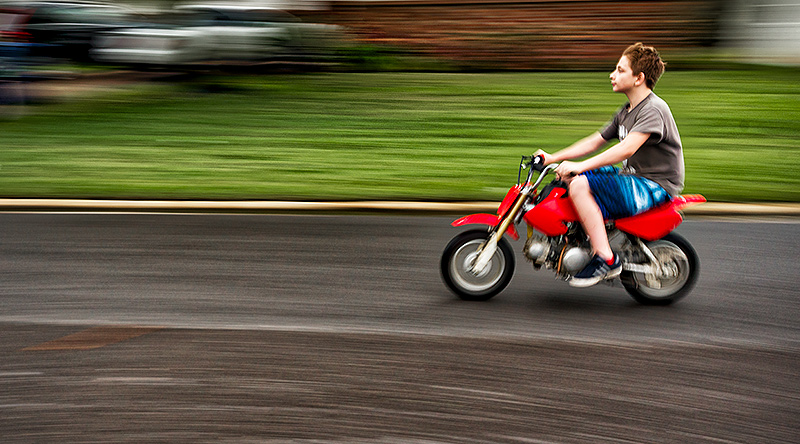 After hearing the revved-up sound of this motor bike buzzing up and down our street, I discovered it was our new neighbor, 12-year-old Brandon. This image was made by panning the camera in sync with the the direction and speed of dirt bike.